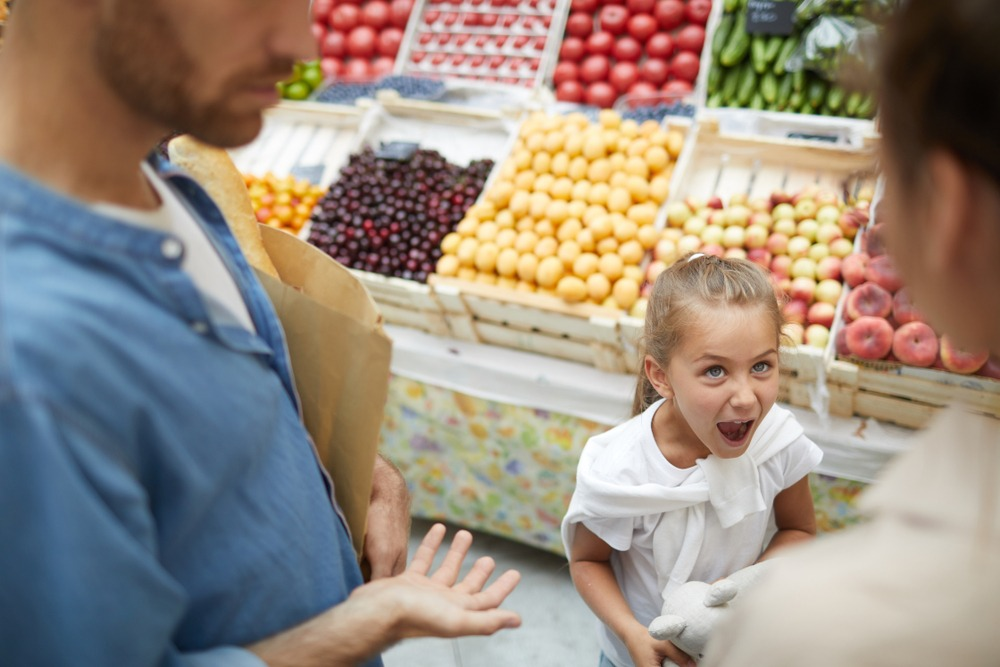 Young child having a temper tantrum at the supermarket as parents look on